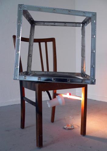 WIR MACHEN ES UNS SCHÖN (DESTILLATOR) / WE MAKE IT OUR BEAUTIFUL (distiller). 2009, chair, metal, lamp, mirror, glass filled with alcohol Praline, 110 x 70 x 40 cm /WIR MACHEN ES UNS SCHÖN (DESTILLATOR). 2009, Chaise, métal, lampe, miroir, verre, l'alcool de praline, 110 x 70 x 40 cm