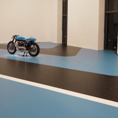 Blue line #2. 2014, painting in situ, Museum of Contemporary Art of Lyon, scale 1 reproduction of Paul Ricard's circuit. Moto Blue Line placed on the paint / Blue line #2. 2014, peinture in situ, Musée d'Art Contemporain de Lyon, reprise échelle 1 d'un morceau d'îlot du circuit Paul Ricard. Moto Blue Line posée sur la peinture